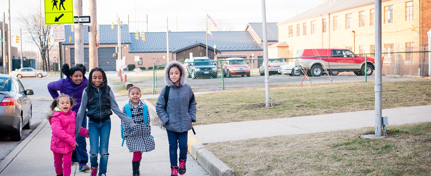 girls walking with sign behind